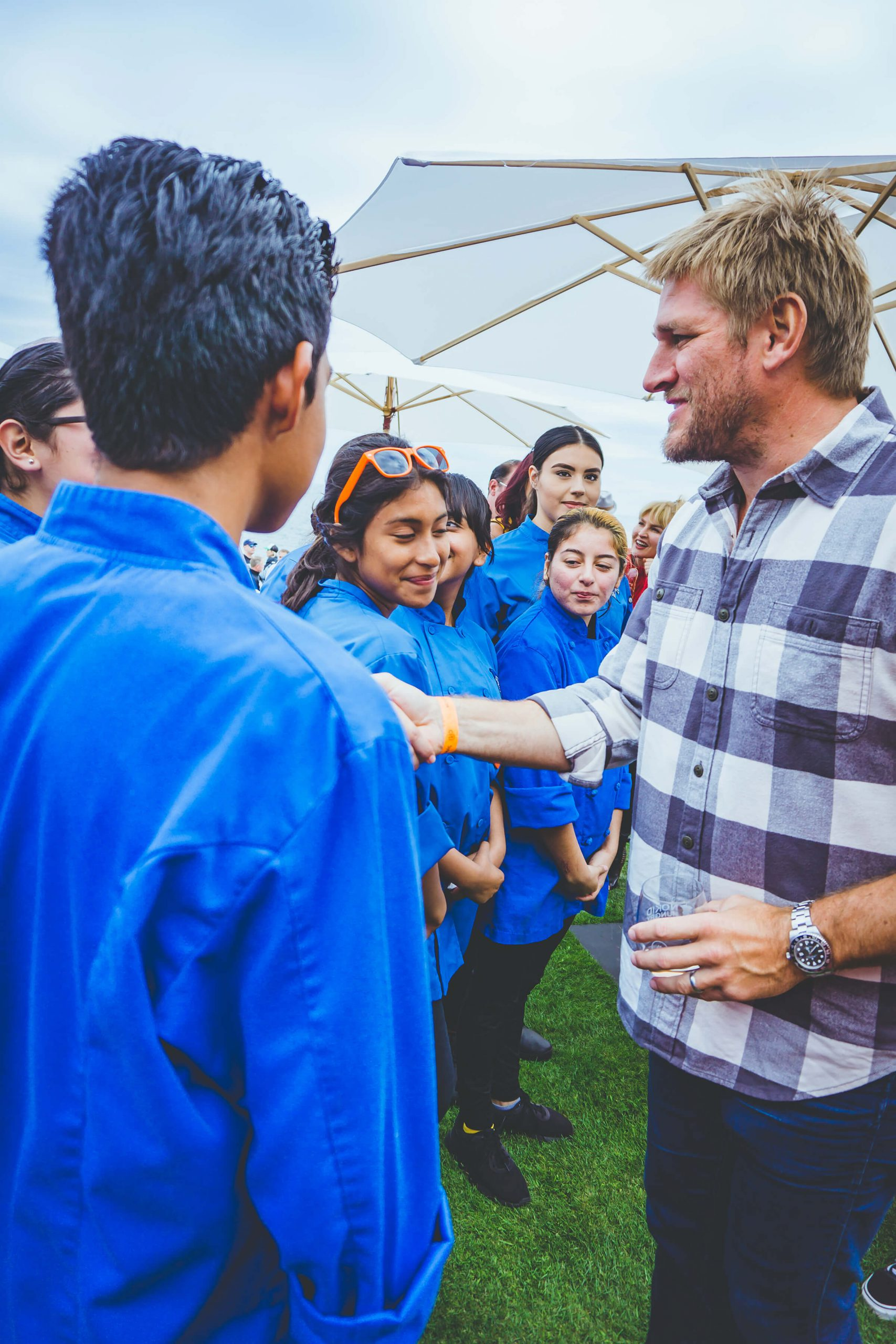 Professional chef Curtis Stone greets a line of aspiring young chefs at an outdoor function.