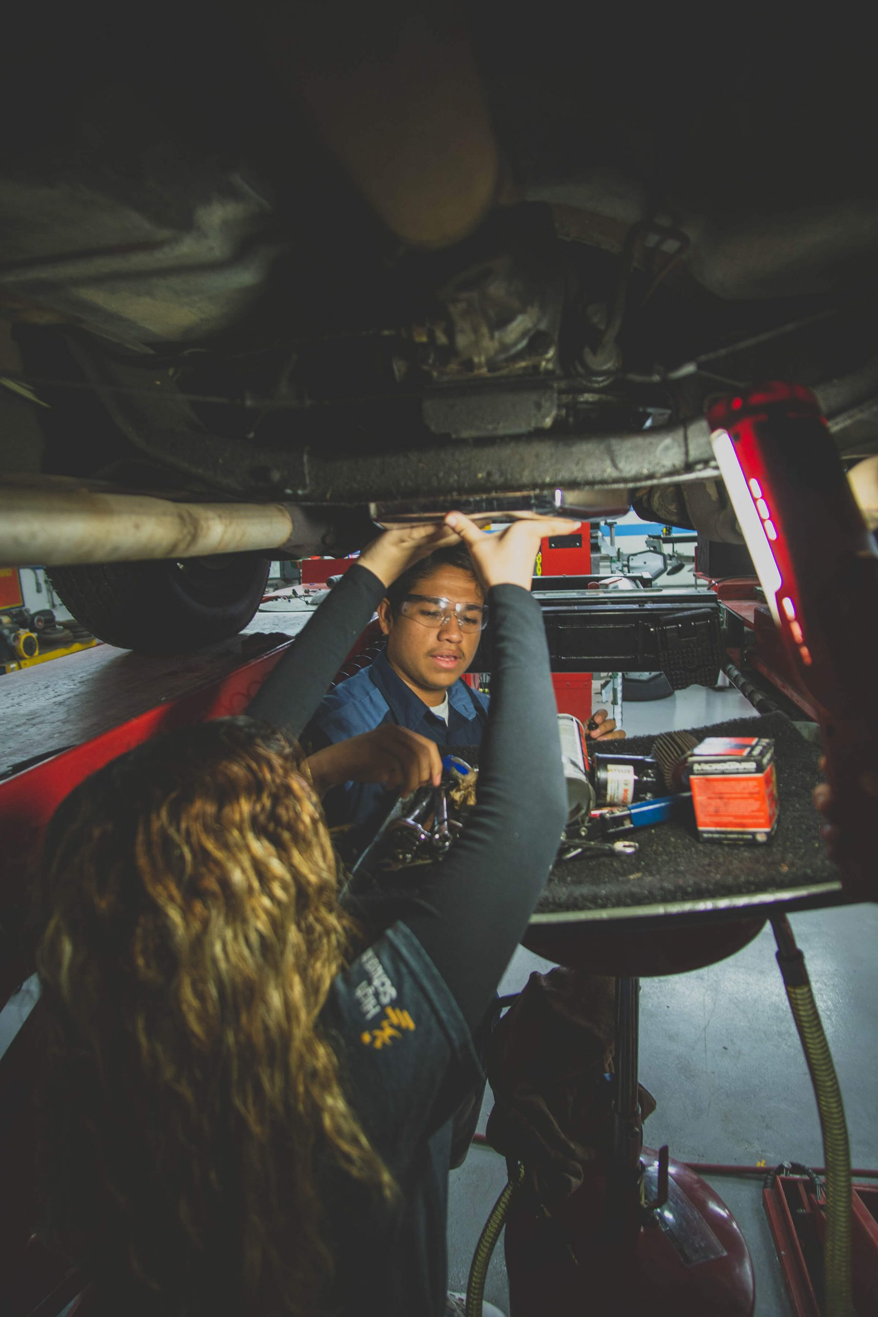 Students work under a raised automotive vehicle in a mechanic garage.