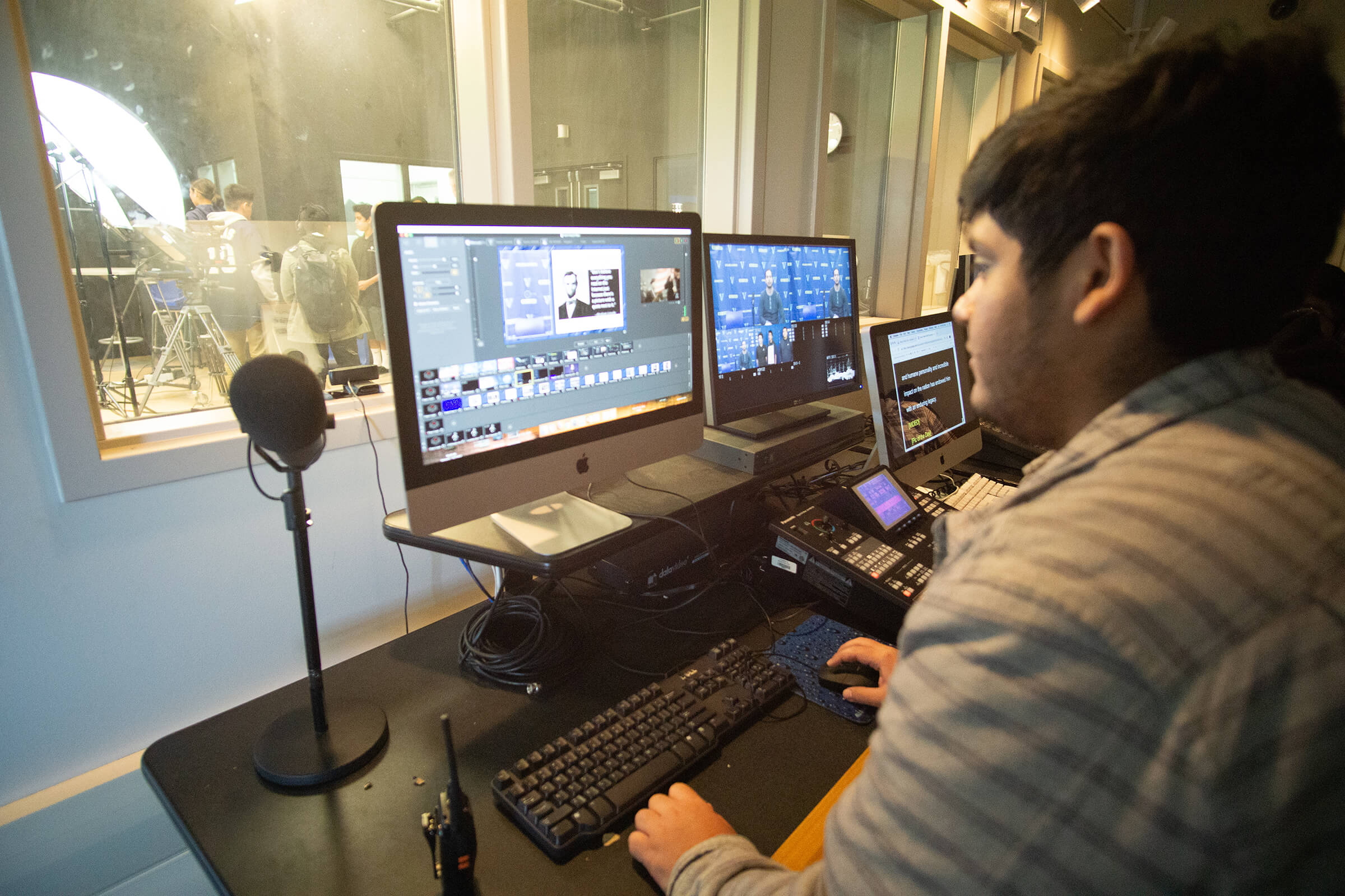 Broadcast students review footage while editing a live recording studio.