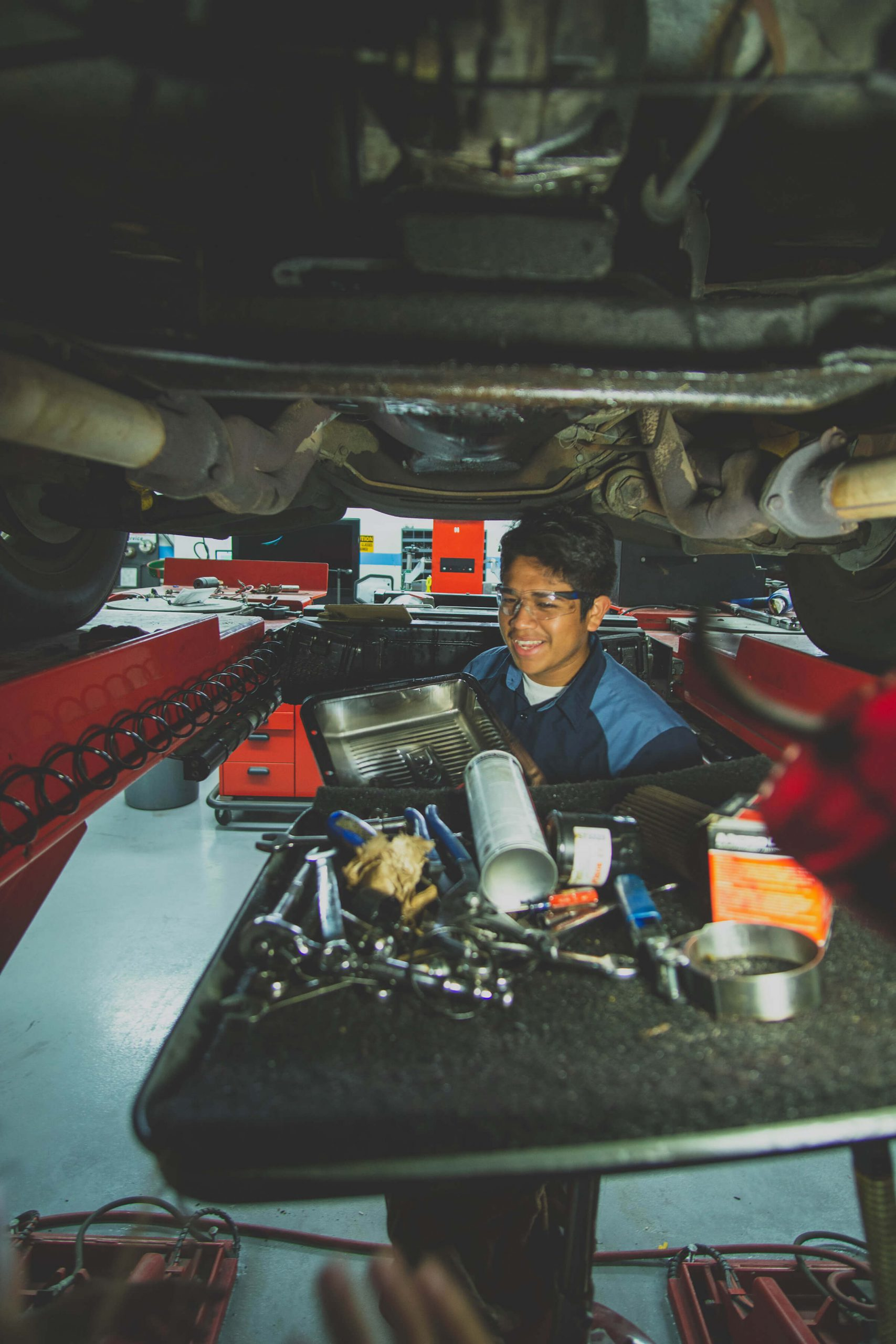 Under a raised automotive vehicle, a young mechanic student changes the oil.